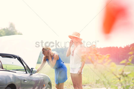 On the road : Woman using cell phone while friend examining broken down car