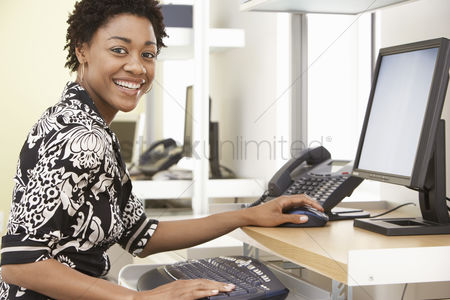 Cheerful : Woman using computer in office portrait