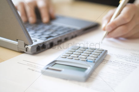 Business : Woman using laptop and calculator close up