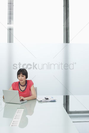 Office worker : Woman using laptop in modern cubicle