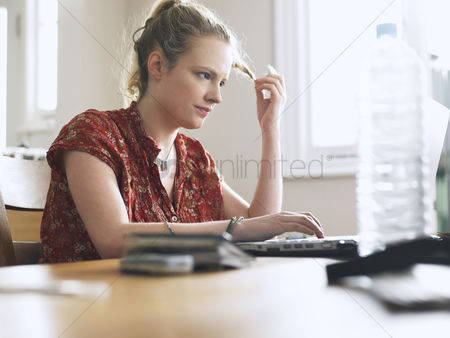 Ponytail : Woman using laptop sitting at dining table low angle view