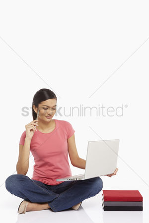 Portability : Woman using laptop while sitting on the floor  contemplating