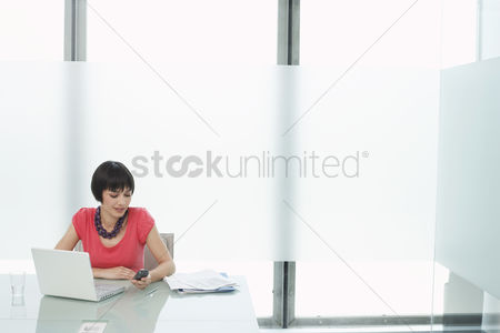 Cell phone : Woman using mobile phone and laptop in modern cubicle