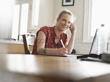 Ponytail : Woman using mobile phone sitting at dining table low angle view