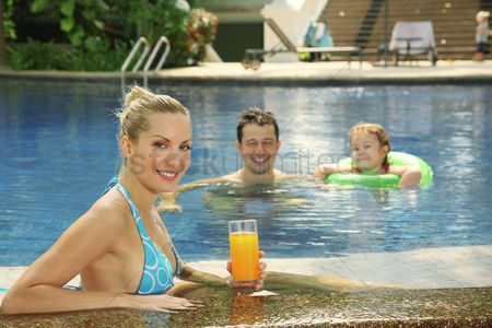 Eastern european ethnicity : Woman with a glass of orange juice at the edge of pool