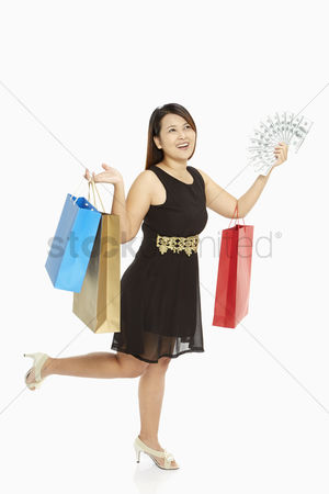 Spending money : Woman with a lot of money carrying paper bags