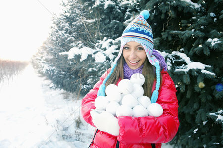 Cold temperature : Woman with an armful of snowballs