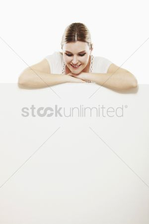 Cardboard cutout : Woman with both arms resting on blank placard  looking down
