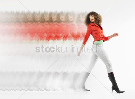 Curly hair : Woman with curly hair walking  in studio multiple exposure