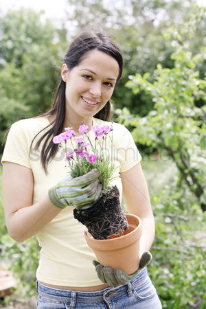 Hobby : Woman with gardening gloves holding a pot flower