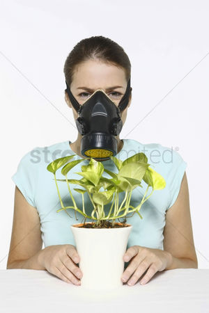 Frowning : Woman with gas mask holding potted plant