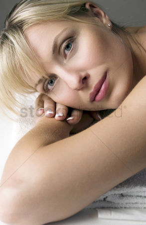 Lying forward : Woman with her head resting on a stack of towels