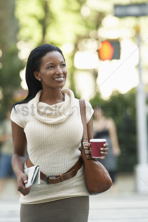 Females : Woman with newspaper and coffee cup walking in street