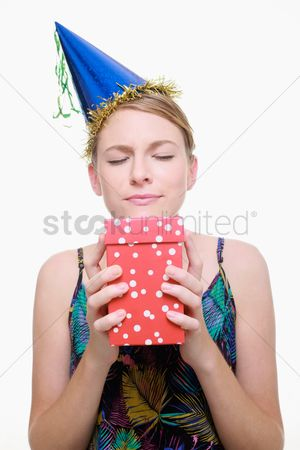 Birthday present : Woman with party hat holding her present with her eyes closed