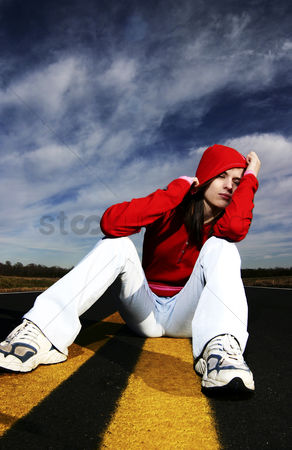 Fashion : Woman with red hooded jacket sitting in the middle of the road