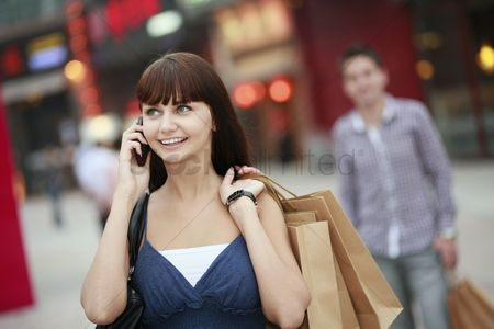Spending money : Woman with shopping bags talking on the phone