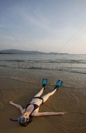 Diving : Woman with snorkeling gear lying on the beach