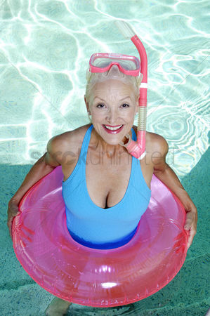 Retirement : Woman with snorkeling goggles and inflatable ring standing in the swimming pool