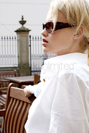 Composed : Woman with sunglasses sitting on the bench