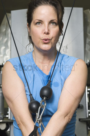 Posed : Woman working out on weightlifting machine