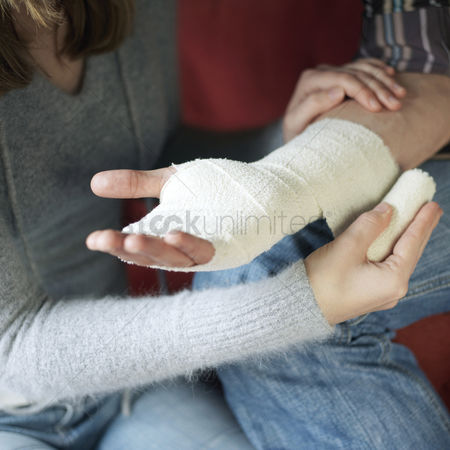 Medication : Woman wrapping man s injured hand