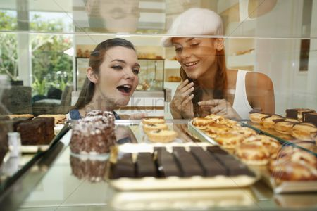 Choosing : Women looking through display case at variety of cakes and tarts