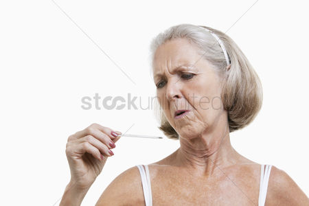 Thermometer : Worried senior woman checking thermometer against white background