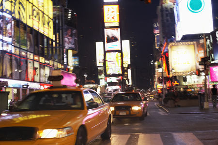 Travel : Yellow taxis on city street at night