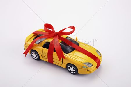 Toy : Yellow toy car gift wrapped with red ribbon