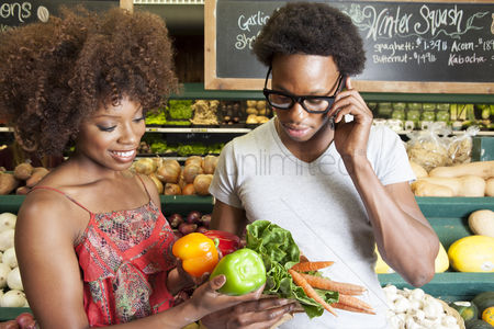 Variety : Young african american couple buying vegetables at supermarket