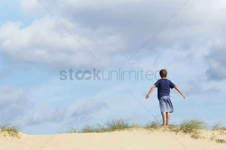Travel : Young boy standing on sand dune in wind with arms outstretched back view