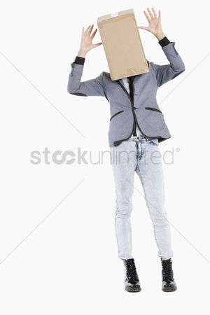 Cardboard cutout : Young boy with box covered over his face and hands raised over gray background