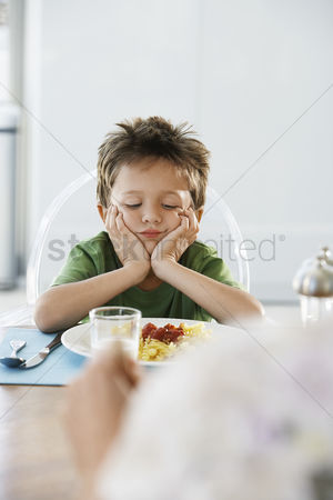 Moody : Young boy with head in hands at dinner table