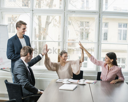 Three quarter length : Young business team doing high five at conference table