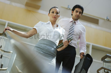 Stairs : Young business woman and business man walking down stairs