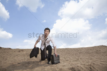 Land : Young businessman kneeling in the desert and holding a briefcase  exhausted