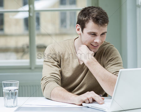 Internet : Young businessman using laptop at desk in office