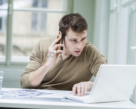 Czech republic : Young businessman using laptop while on call