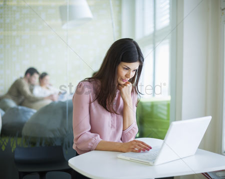 Women : Young businesswoman using laptop at office table