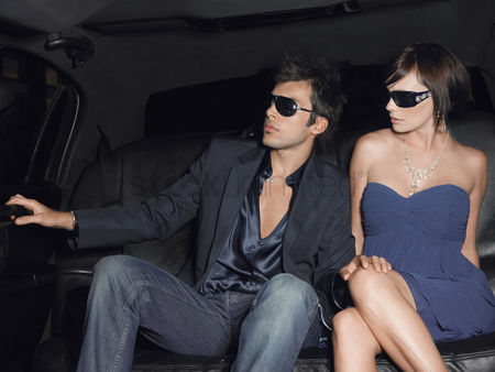 Car : Young couple in backseat of limousine wearing evening dress and sunglasses