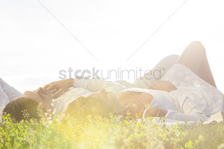 Grass background : Young couple lying on grass against clear sky