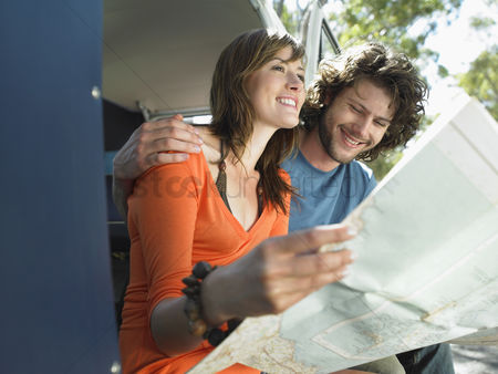 Gladness : Young couple reading map on road trip