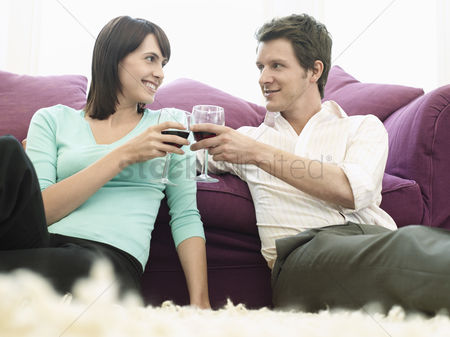Toasting : Young couple relaxing on sofa toasting with wine