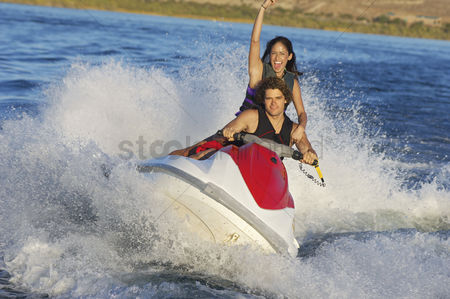 Arm raised : Young couple riding jetski on lake