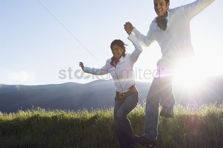 Smiling : Young couple running and jumping in mountain field