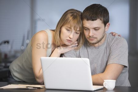 Interior : Young couple sit at laptop in kitchen