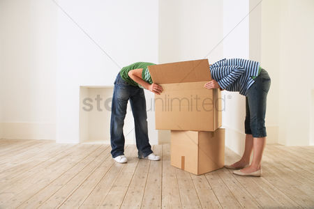 Interior : Young couple unpacking box in new home with  faces hidden