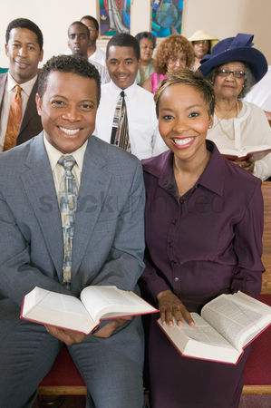 Religion : Young couple with bibles sitting on church pews portrait