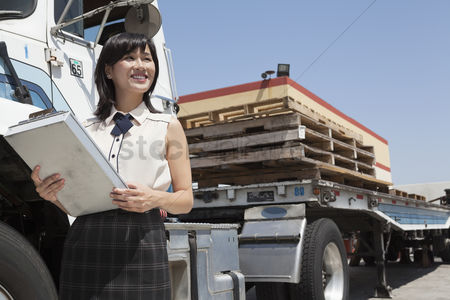 Land : Young female holding clipboard while standing next to flatbed truck