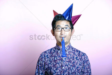 Excited : Young geeky asian man wearing many party hats